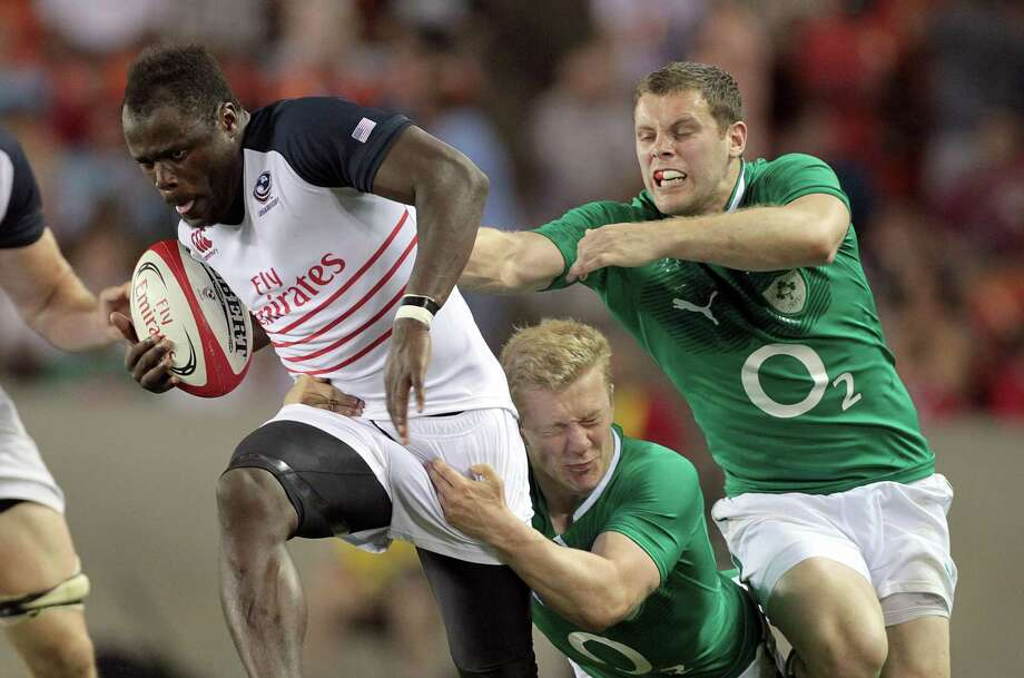 USA Rugby wing Takudzwa Ngwenya, left, does his best to escape the clutches of his counterparts from Ireland during an international match attended by a record crowd of 20,181 at BBVA Compass Stadium. Photo: Nick De La Torre, Staff / © 2013  Houston Chronicle