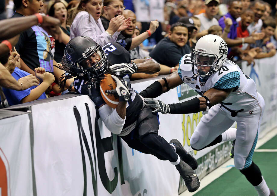 San Antonio receiver Brent Holmes crashes into the sideline inside the five yard line after a catch against defender Jeremy Kellem setting up the only home team score in the first half as the Talons host the Arizona Rattlers in the Alamodome on June 8, 2013. Photo: TOM REEL