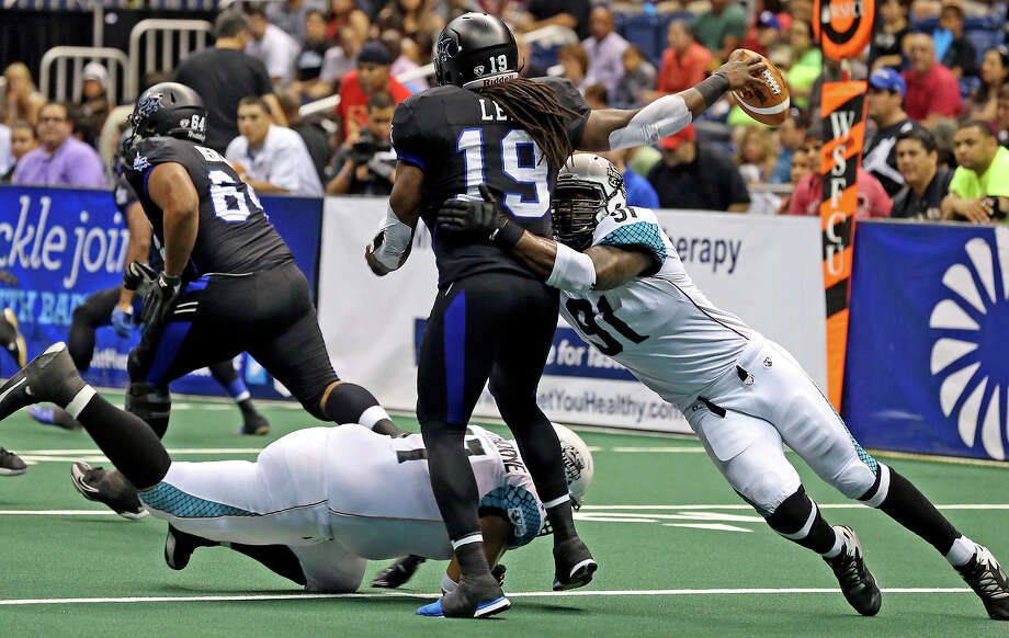 Rattler players force the ball out of the hands of quarterback Xavier Lee as the Talons host the Arizona Rattlers in the Alamodome on June 8, 2013. Photo: Tom Reel, San Antonio Express-News