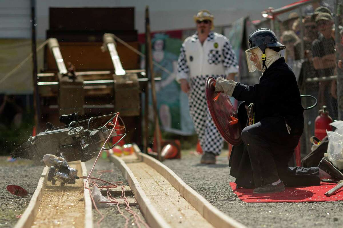 Track officials take cover as two power tool racers collide mid-track during the annual Georgetown Carnival Saturday, June 8, 2013, in the Georgetown neighborhood of Seattle. The quirky event featured live music, burlesque and crafting.
