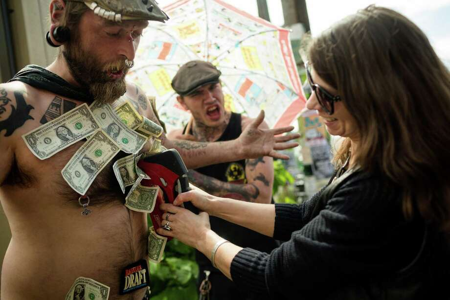 Digger Sadu Hobo, left, lets a woman staple a dollar to his chest at the annual Georgetown Carnival Saturday, June 8, 2013, in the Georgetown neighborhood of Seattle. The quirky event featured live music, burlesque and crafting. Photo: JORDAN STEAD, SEATTLEPI.COM / SEATTLEPI.COM