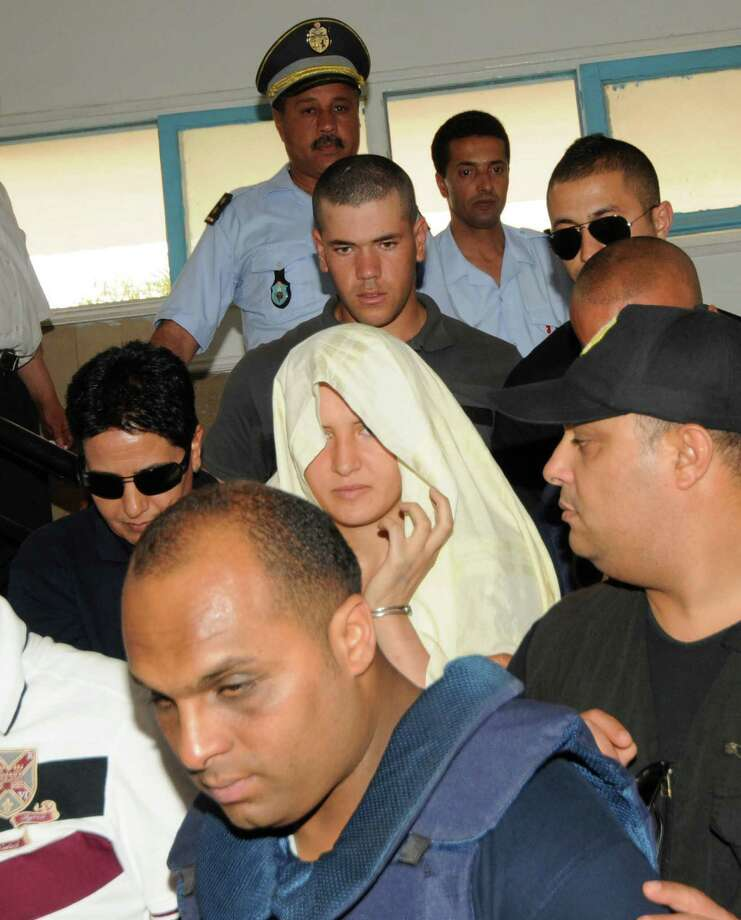 Tunisian feminist activist Amina Sboui, hidden by a veil, is escorted by police officers as she leaves the courthouse in Kairouan, Tunisia, Wednesday, June 5, 2013.  Sboui, a Tunisian member of radical Ukrainian feminist group Femen, scandalized the country by posting topless photos of herself protesting for women's rights in March. She later attempted another protest May 19 in the religious center of Kairouan, where she was arrested. On Wednesday, she appeared before an investigating judge in Kairouan who is considering the charges of public indecency, desecrating a cemetery and belonging to a band of malefactors seeking to damage public property. Photo: AP