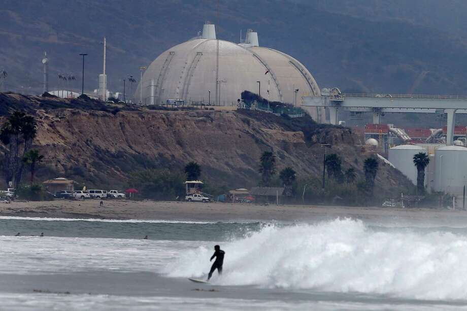 A surfer rides a wave in front of the San Onofre nuclear power plant Friday, June 7, 2013, in San Onofre, Calif. The troubled power plant on the California coast is closing after an epic 16-month battle over whether the twin reactors could be safely restarted with millions of people living nearby, officials announced Friday. Photo: AP