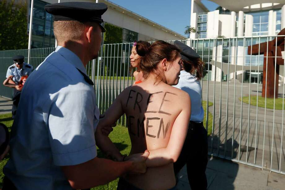 "Activists from the women's movement Femen are being stopped by police officers during a protest in front of the German chancellery ahead of the visit of Tunisian Prime Minister Ali Laarayedh in Berlin, Friday, June 7, 2013. Three topless Femen protesters pleading for Angela Merkel to push for the release of four fellow activists jailed in Tunisia. The women chanted ""Merkel free Femen"" and two women had painted the names of the activists jailed in Tunisia across their bare chests. Three European Femen demonstrators were arrested last month in Tunis for demonstrating for the release of a Tunisian activist who faces possible charges of public indecency for posting topless photos of herself protesting for women's rights. Photo: AP"