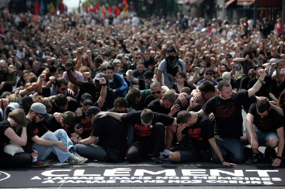 Protestors pay respects to Clement Meric, at a demonstration in honour of Clement Meric, an anti-fascist activist killed in a fight with skinheads in Paris on June 5,   in Paris, Saturday, June 8, 2013. The Paris prosecutor said Saturday he is seeking an investigation for murder against a 20-year-old far-right militant suspected of being involved in the killing of an anti-fascist activist in Paris this week. Photo: AP