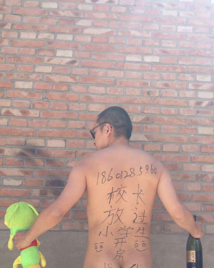"""In this photo taken Wednesday May 29, 2013 and released by Beijing-based poet Wang Zang Monday, June 3, 2013, Wang poses at his work place in Beijing with the Chinese characters """"Principal, get a room with me. Leave the young students alone,"""" scribbled on his back while holding a toy and a liquor bottle. The unusual outpouring is in response to a recent spate of sex abuse cases, including that of a school principal who spent the night in a hotel room with four underage girls. Artists, activists, university students and police officers are photographing themselves - some nude and provocatively posed, some angry and menacing - with the message. Photo: AP"""