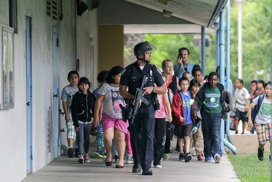 A Santa Monica police officer leads children on a field trip from Citizens of the World Charter School in Los Angeles out of Santa Monica College, where they had gone for a planetarium show, following a shooting in the area, in Santa Monica, Calif., Friday, June 7, 2013. Two people were found dead Friday in a burned home near the campus, where someone sprayed a street corner with gunfire. Photo: AP