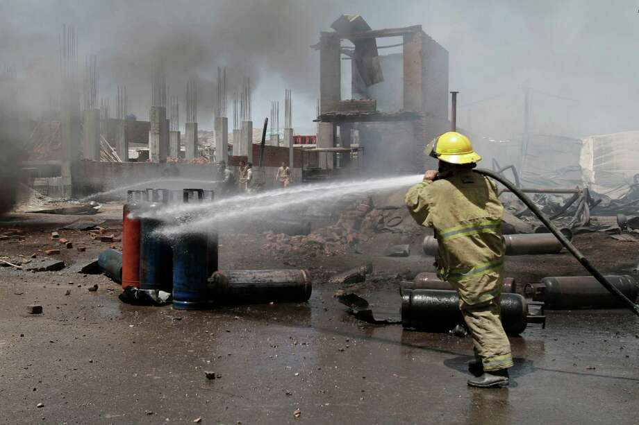 An Afghan firefighter sprays water at the scene of a propane gas explosion accident in Jalalabad, east of Kabul, Afghanistan, Friday, June 7, 2013. About 30 shops at the market were burnt down in the fire. Three people were injured, an official said. Photo: AP