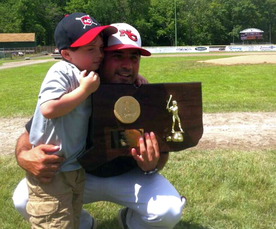New Canaan coach Mitch Hoffman poses with with his son and the Class L championship trophy after defeating Waterford 3-0 in the baseball championship game Sunday, June 9, 2013 at Palmer Field. (Photo by Scott Ericson)