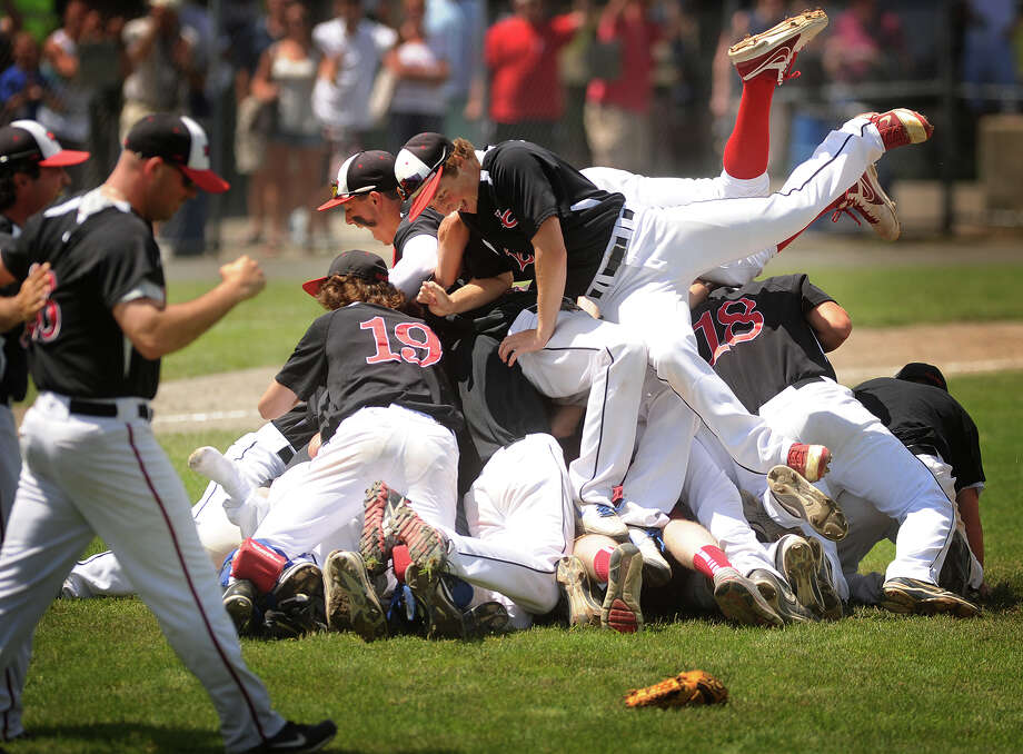 New Canaan player leap into a pile on the mound after securing the final out in their 3-0 victory over Waterford in the Class L baseball championship game at Palmer Field in Middletown, Conn. on Sunday, June 9, 2013. Photo: Brian A. Pounds / Connecticut Post