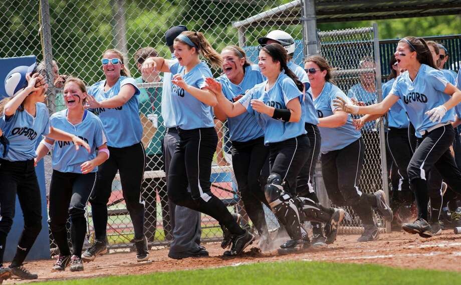 The Oxford high school team celebrates as their teammate Makena Hillman crosses home plate scoring the game winning run against Terryville high school in the CIAC class S softball championship game played at West Haven high school, West Haven, CT on Sunday June 9th, 2013. Photo: Mark Conrad / Connecticut Post Freelance
