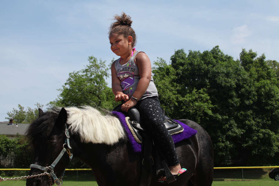 Lea Duzant, 5, of Trumbull, gets a pony ride from Runabout Farm in Stamford during Black Rock Day in Bridgeport, Conn. on Sunday, June 9, 2013. Runabout Farm is a animal rescue farm. Photo: Unknown, B.K. Angeletti / Connecticut Post freelance B.K. Angeletti