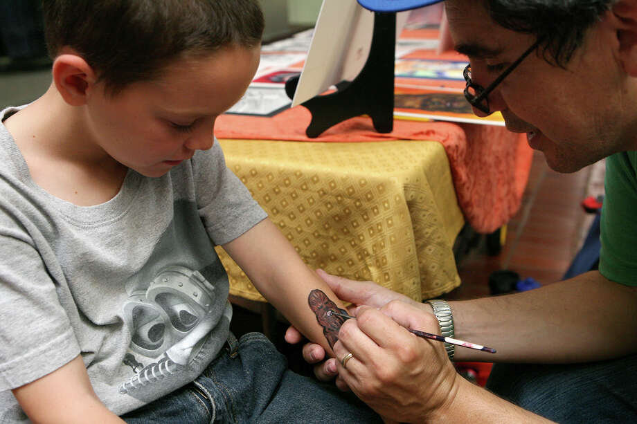 Alex Gonzales, 8, has Chewbacca drawn on his arm June 9, 2013 by Alberto Ramirez of Arriba Arte Studios during the NDG Sci-Fest at Wonderland of the Americas. Photo: Cynthia Esparza, For The San Antonio Express-News / For San Antonio Express-News