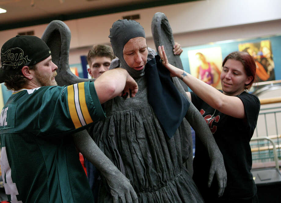 Scott Lund (left) and Jill Fiebig help Shannon McCarthy put on her wings to become a weeping angel from Doctor Who during the NDG Sci-Fest June 9, 2013 at Wonderland of the Americas. Photo: Cynthia Esparza, For The San Antonio Express-News / For San Antonio Express-News