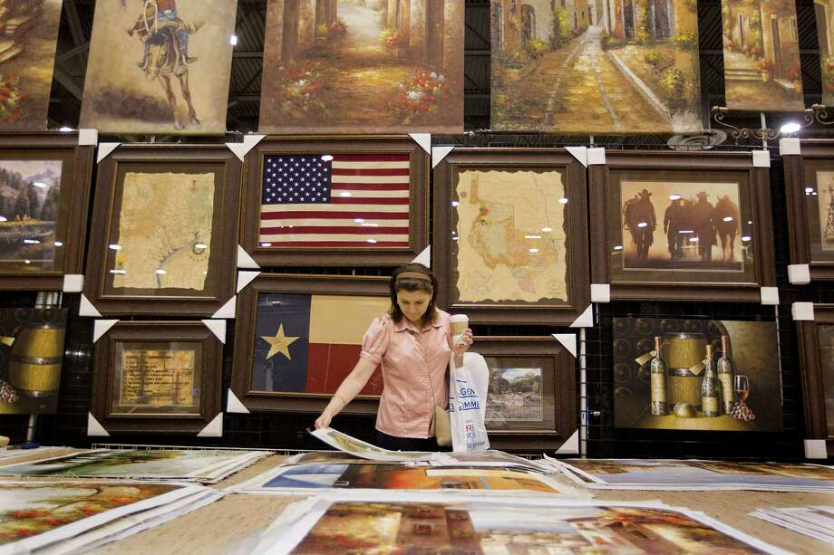 Tyra Hessel of Houston looks at oil paintings in the Oil Paintings and Frames  Warehouse exhibit booth during the 21st Annual New Home and Remodeling Show at Reliant Center Sunday, June 9, 2013, in Houston. 