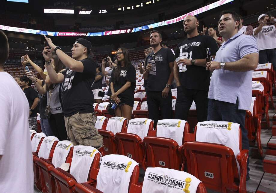 A small gathering of Spurs fans watch shoot around before Game 2 of the NBA Finals between the Spurs and the Miami Heat at the American Airlines Arena on Sunday, June 9, 2013. (Kin Man Hui/San Antonio Express-News)