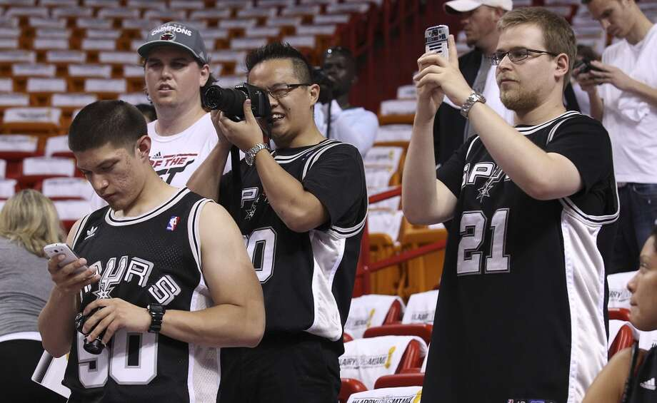 Donning their Spurs jerseys, fans Ian Smith (from right) from New Jersey, Hong Nguyen from Australia and Rene Rendon from San Antonio watch the shoot around before Game 2 of the NBA Finals between the Spurs and the Miami Heat at the American Airlines Arena on Sunday, June 9, 2013. All three flew in to Miami to watch the game. (Kin Man Hui/San Antonio Express-News)