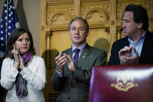 HARTFORD, CT - APRIL 4:  Parents of Sandy Hook School shooting victims (L to R) Jackie Barden, Mark Barden, and Neil Heslin, applaud before the signing of a gun-control bill at the Connecticut Capitol on April 4, 2013 in Hartford, Connecticut. After mo