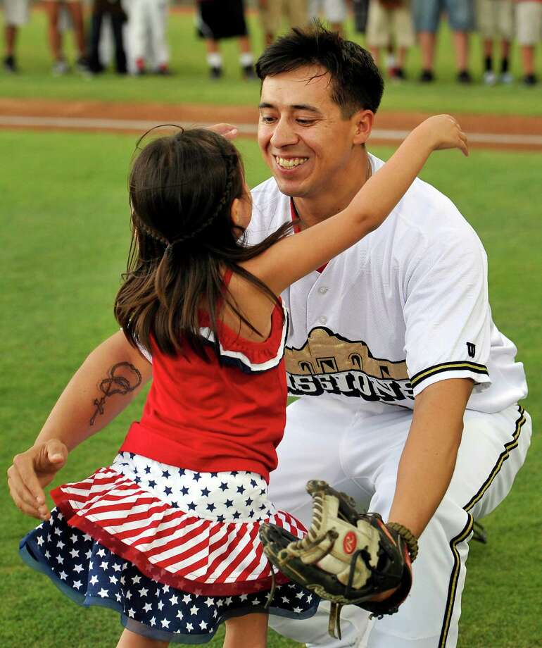 Five-year-old Hailey Sandoval, left, hugs her father, Army Staff Sgt. Alvino Sandoval, before a Texas League baseball game between the Corpus Christi Hooks and the San Antonio Missions, Sunday, June 9, 2013, at Wolff Stadium in San Antonio. Hailey threw the ceremonial first pitch of the game to her father, who, disguised by a catcher's mask, surprised Hailey at the game with his return from active duty in Afghanistan. (Darren Abate/For the Express-News) Photo: Darren Abate, San Antonio Express-News