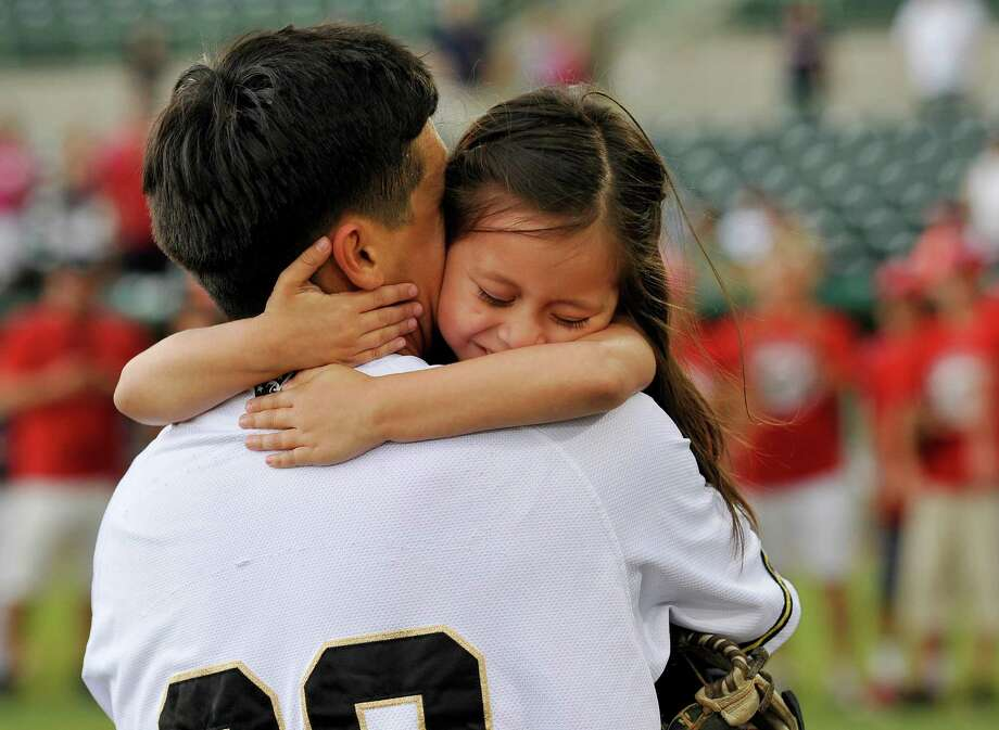 Five-year-old Hailey Sandoval, right, hugs her father, Army Staff Sgt. Alvino Sandoval, before a Texas League baseball game between the Corpus Christi Hooks and the San Antonio Missions, Sunday, June 9, 2013, at Wolff Stadium in San Antonio. Hailey threw the ceremonial first pitch of the game to her father, who, disguised by a catcher's mask, surprised Hailey at the game with his return from active duty in Afghanistan. (Darren Abate/For the Express-News) Photo: Darren Abate, San Antonio Express-News