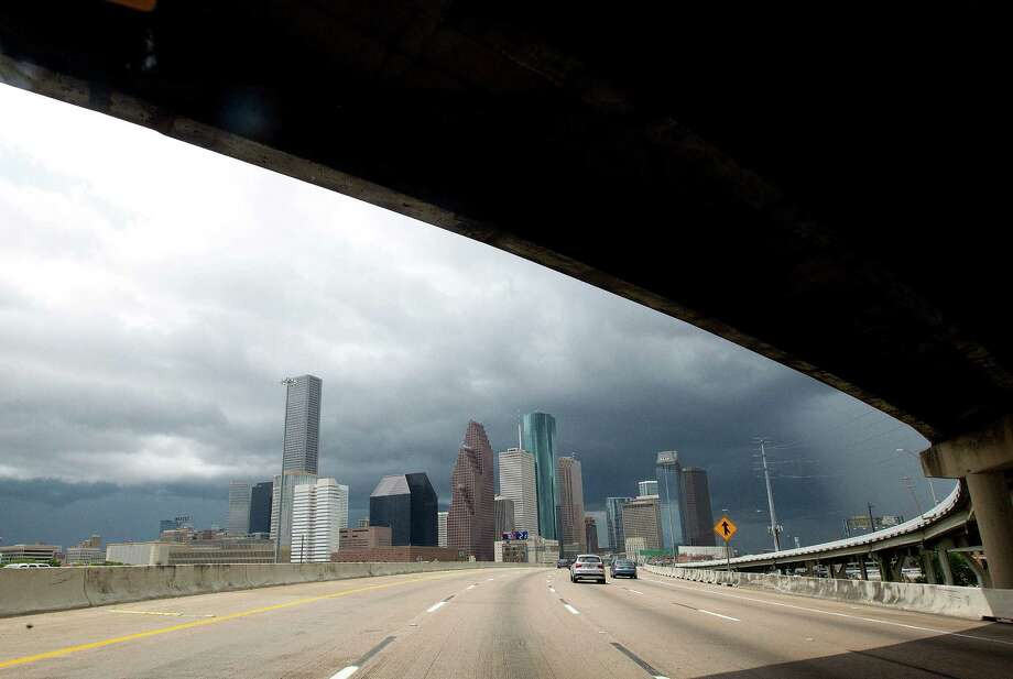 Rain showers move over the downtown skyline Sunday, June 9, 2013, in Houston. Photo: Johnny Hanson, Houston Chronicle / © 2013  Houston Chronicle