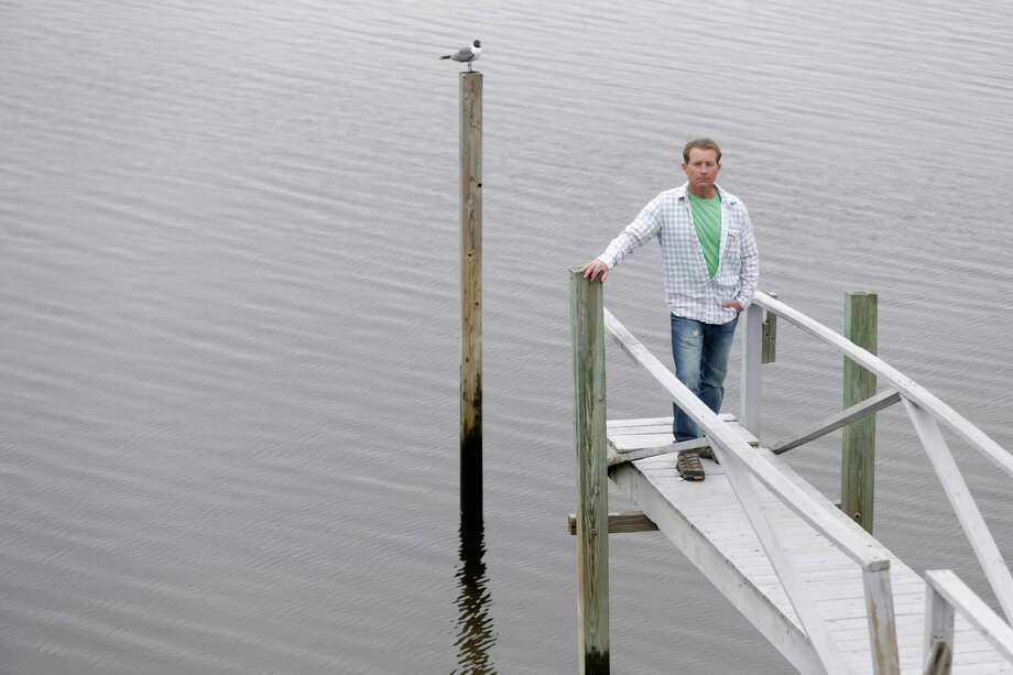 In  this Thursday, April 11, 2013, photo, Dan Mundy poses for a picture on his dock in the Broad Channel section of Queens, New York. As people finish up repairs to their waterlogged houses, officials are warning them that they must prepare for the future and raise their homes high above the flood plain or they could face up to $30,000 a year in flood insurance costs. (AP Photo/Seth Wenig) Photo: Seth Wenig