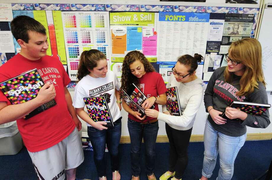 Burnt Hills-Ballston Lake High School Yearbook staff members: Tyus Hadcock, left, Breann Litway, Caley Pantalone, Venissa Chen, and Gabriella Marchetti, right, look through their 2013 yearbooks Friday, June 7, 2013, in Burnt Hills, N.Y. (Will Waldron/Times Union) Photo: Will Waldron
