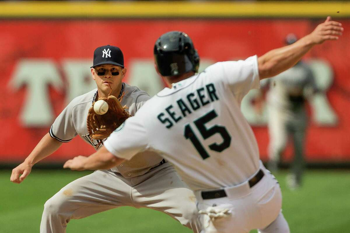 Kyle Seager, right, unsuccessfully slides into second base during the ninth inning of a game against the New York Yankees Sunday, June 9, 2013, at Safeco Field in Seattle. Nearly 44,000 people attended the sunny day game, and the New York Yankees beat the Mariners 2-1.