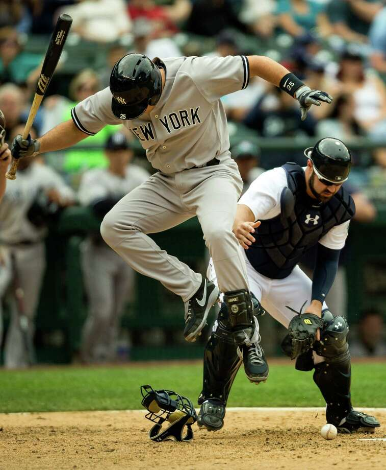 New York Yankees player Mark Teixeira, left, leaps out of the way of a glancing, grounded ball that he sliced downward into home plate during a game Sunday, June 9, 2013, at Safeco Field in Seattle. Nearly 44,000 people attended the sunny day game, and the New York Yankees beat the Mariners 2-1. Photo: JORDAN STEAD, SEATTLEPI.COM / SEATTLEPI.COM