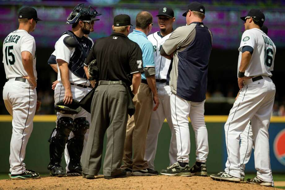 Mariners officials meet with pitcher Felix Hernandez, center right, at the mound during a game against the New York Yankees Sunday, June 9, 2013, at Safeco Field in Seattle. Nearly 44,000 people attended the sunny day game, and the New York Yankees beat the Mariners 2-1. Photo: JORDAN STEAD, SEATTLEPI.COM / SEATTLEPI.COM