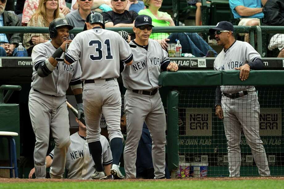 Ichiro Suzuki, second from left, is congratulated by teammates after scoring a run in the eighth inning during a game against the Mariners Sunday, June 9, 2013, at Safeco Field in Seattle. Nearly 44,000 people attended the sunny day game, and the New York Yankees beat the Mariners 2-1. Photo: JORDAN STEAD, SEATTLEPI.COM / SEATTLEPI.COM