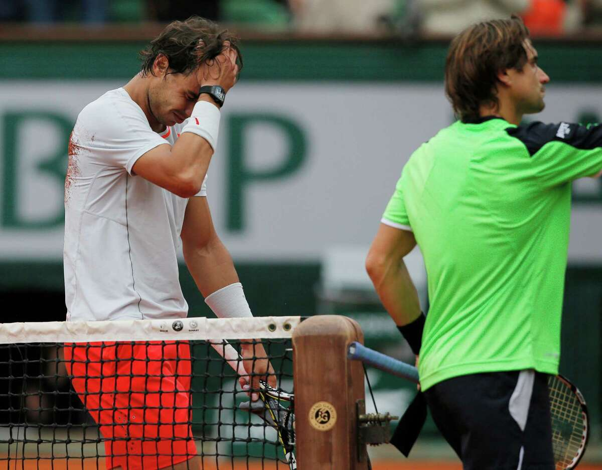 Spain's Rafael Nadal, left, holds his head after defeating compatriot David Ferrer, right, in three sets 6-3, 6-2, 6-3, in the final of the French Open tennis tournament, at Roland Garros stadium in Paris, Sunday June 9, 2013. (AP Photo/Michel Spingler)