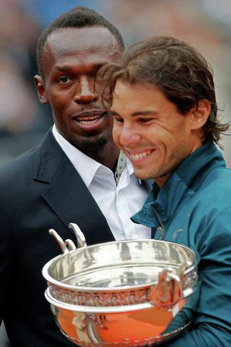 Jamaica's Usain Bolt smiles as Spain's Rafael Nadal holds the trophy after winning against compatriot David Ferrer in three sets 6-3, 6-2, 6-3, in the final of the French Open tennis tournament, at Roland Garros stadium in Paris, Sunday June 9, 2013. (AP Photo/Christophe Ena) Photo: Christophe Ena