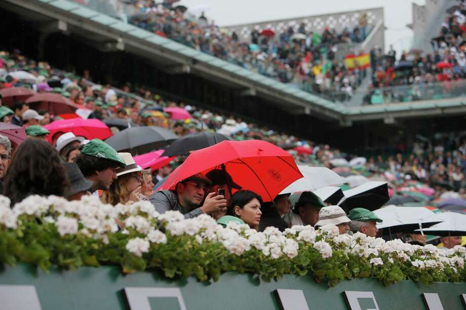 A spectator under a red umbrella takes images with a smart phone as Spain's Rafael Nadal returns against compatriot David Ferrer in the final of the French Open tennis tournament, at Roland Garros stadium in Paris, Sunday June 9, 2013. (AP Photo/Michel Spingler) Photo: Michel Spingler