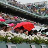 A spectator under a red umbrella takes images with a smart phone as Spain's Rafael Nadal returns against compatriot David Ferrer in the final of the French Open tennis tournament, at Roland Garros stadium in Paris, Sunday June 9, 2013. (AP Photo/Michel Spingler)