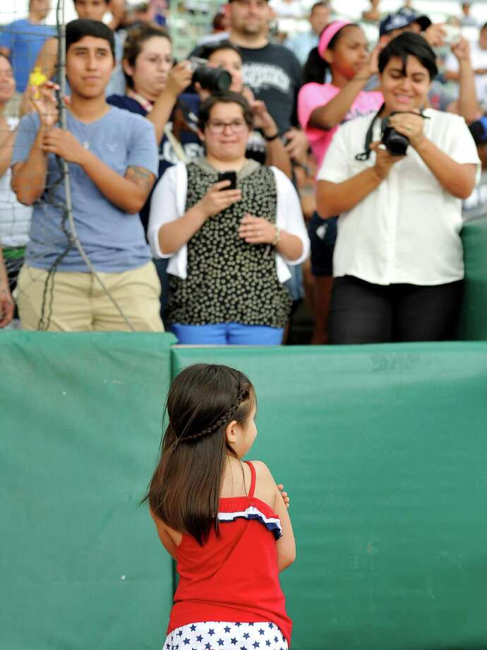Five-year-old Hailey Sandoval stands as family members take photos of her before a Texas League baseball game between the Corpus Christi Hooks and the San Antonio Missions, Sunday, June 9, 2013, at Wolff Stadium in San Antonio. Hailey threw the ceremonial first pitch of the game to her father, Army Staff Sgt. Alvino Sandoval, who surprised Hailey at the game with his return from active duty in Afghanistan. (Darren Abate/For the Express-News) Photo: Darren Abate, San Antonio Express-News