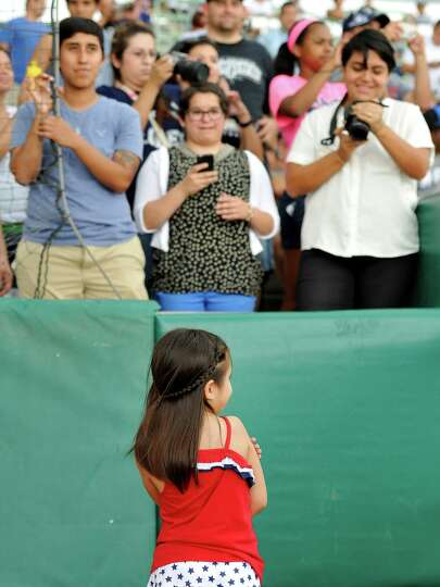 Five-year-old Hailey Sandoval stands as family members take photos of her before a Texas League base