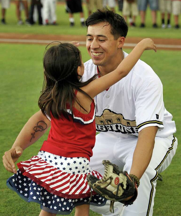 Five-year-old Hailey Sandoval hugs her father, Army Staff Sgt. Alvino Sandoval, before a Texas League baseball game between the Corpus Christi Hooks and the San Antonio Missions on Sunday.TOP LEFT: Five-year-old Hailey Sandoval throws the ceremonial first pitch.                 LEFT: Hailey Sandoval hugs her father. Photo: Photos By Darren Abate / For The San Antonio Express-News