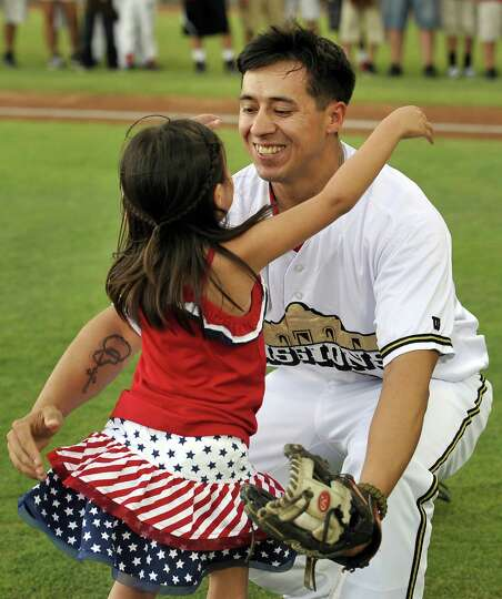 Five-year-old Hailey Sandoval hugs her father, Army Staff Sgt. Alvino Sandoval, before a Texas Leagu