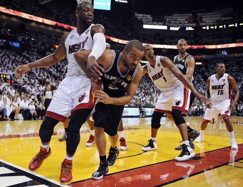 Miami Heat's Dwyane Wade and San Antonio Spurs' Tony Parker fall out of bounds after a play during second half action in Game 2 of the 2013 NBA Finals Sunday June 9, 2013 at American Airlines Arena in Miami, Fla.