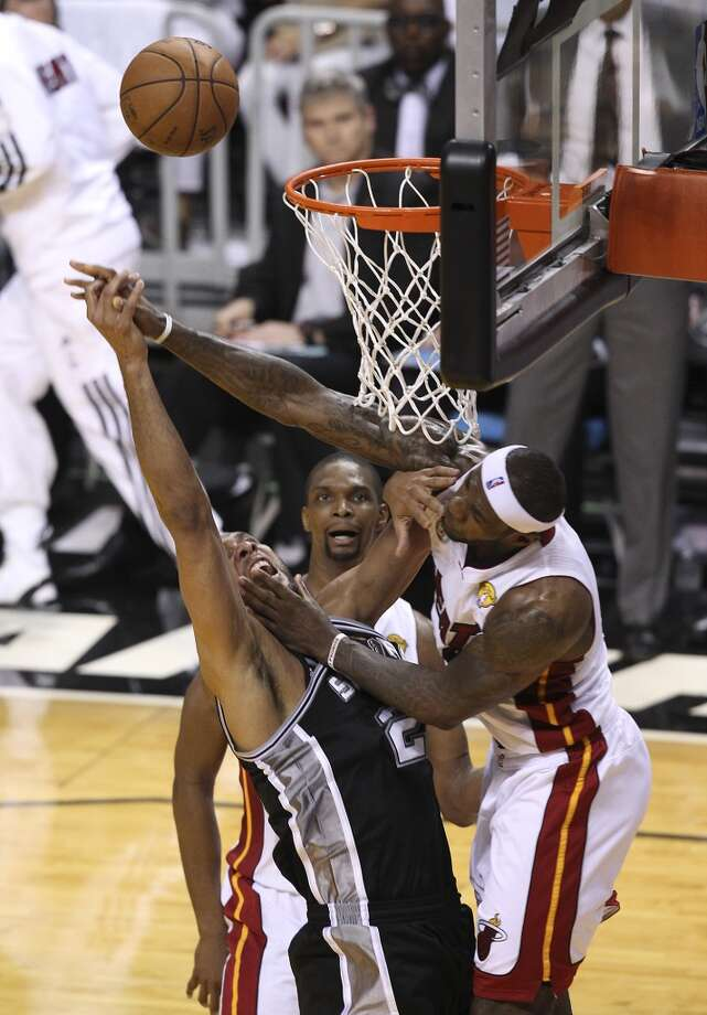 Spurs' Tim Duncan (21) gets contact by Miami Heat's LeBron James (06) during the first half of Game 2 of the NBA Finals at the American Airlines Arena in Miami on Sunday, June 9, 2013. (Kin Man Hui/San Antonio Express-News)