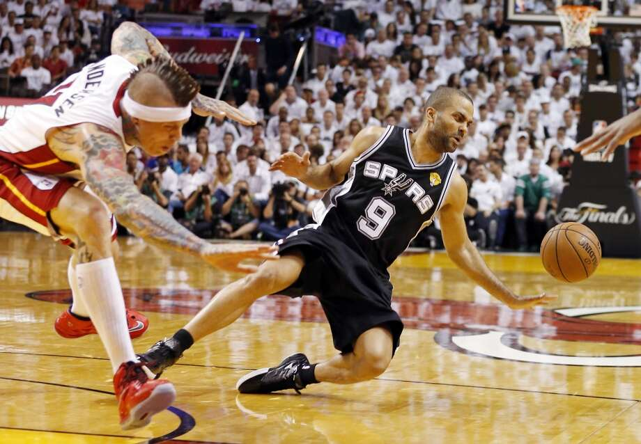 San Antonio Spurs' Tony Parker falls as he drives around Miami Heat's Chris Andersen during first half action in Game 2 of the 2013 NBA Finals Sunday June 9, 2013 at American Airlines Arena in Miami, Fla.