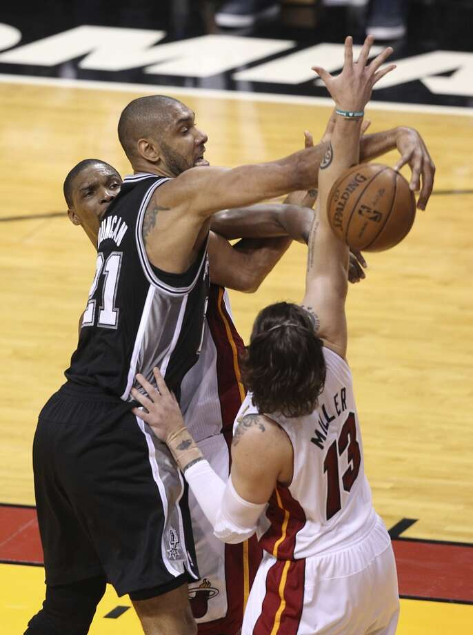 Spurs' Tim Duncan (21) attempts a pass around the Miami Heat's Mike Miller (13) during the first half of Game 2 of the NBA Finals at the American Airlines Arena in Miami on Sunday, June 9, 2013. (Kin Man Hui/San Antonio Express-News)