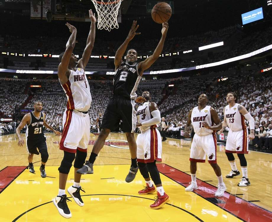 Spurs' Kawhi Leonard (02) attempts to grab a rebound against the Miami Heat's Chris Bosh (01) during the first half of Game 2 of the NBA Finals at the American Airlines Arena in Miami on Sunday, June 9, 2013. (Kin Man Hui/San Antonio Express-News)