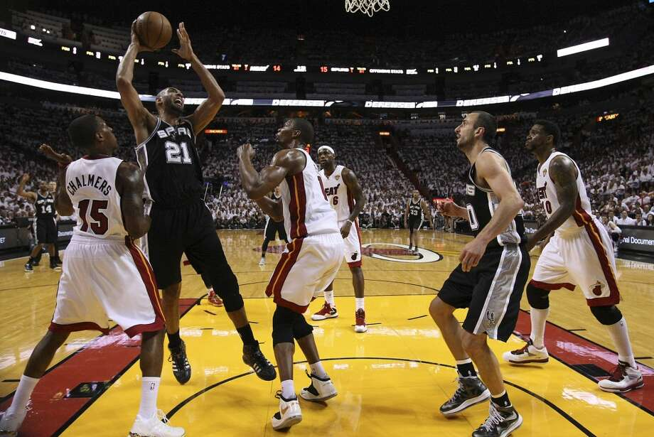 Spurs' Tim Duncan (21) goes up for shot against Miami Heat's Chris Bosh (01) and Mario Chalmers (15) during the first half of Game 2 of the NBA Finals at the American Airlines Arena in Miami on Sunday, June 9, 2013. (Kin Man Hui/San Antonio Express-News)