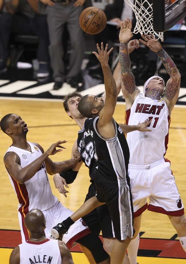 Spurs' Tony Parker (09) drives the lane against the Miami Heat's Chris Andersen (11) and Chris Bosh (01) during the first half of Game 2 of the NBA Finals at the American Airlines Arena in Miami on Sunday, June 9, 2013. (Kin Man Hui/San Antonio Express-News)