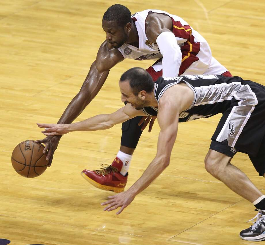 Spurs' Manu Ginobili (20) and Miami Heat's Dwyane Wade (03) run for a loose ball during the first half of Game 2 of the NBA Finals at the American Airlines Arena in Miami on Sunday, June 9, 2013. (Kin Man Hui/San Antonio Express-News)