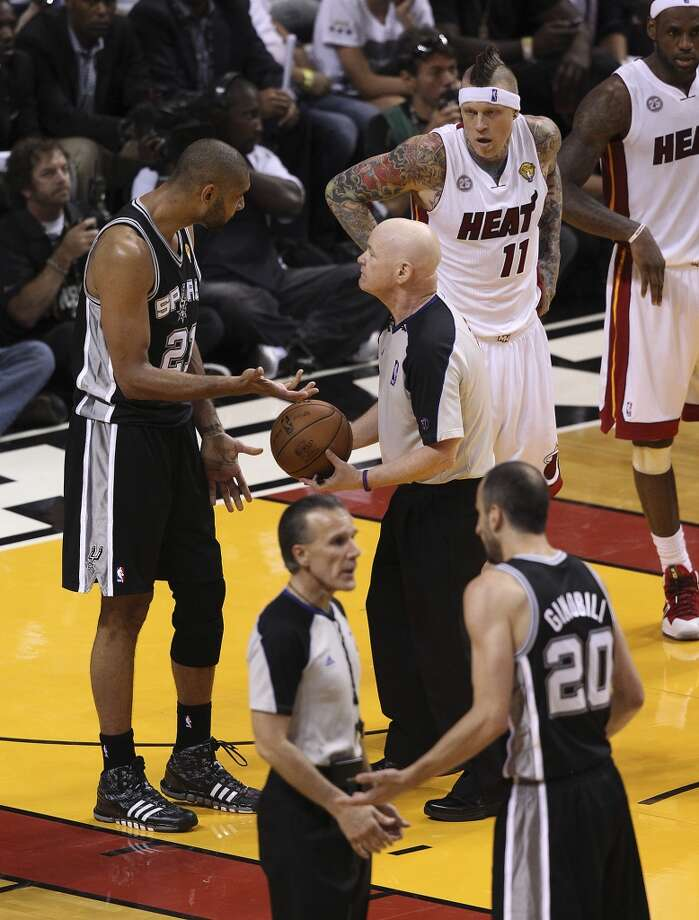 Spurs' Tim Duncan (21) talks to game official Joe Crawford while Manu Ginobili (20) talks to official Ken Mauer during the second half against the Miami Heat in Game 2 of the NBA Finals at the American Airlines Arena in Miami on Sunday, June 9, 2013. (Kin Man Hui/San Antonio Express-News)