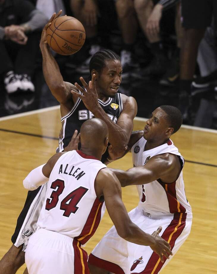 Spurs' Kawhi Leonard (02) looks to pass out of trouble against the Miami Heat's Ray Allen (34) and Mario Chalmers (15) during the second half of Game 2 of the NBA Finals at the American Airlines Arena in Miami on Sunday, June 9, 2013. (Kin Man Hui/San Antonio Express-News)