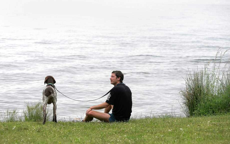 Michael Garrity relaxes with Dosewallips, a 3-year-old German Shorthaired Pointer, after participating in the 14th annual Furry 5k Fun Run and Walk at Seward Park on Sunday, June 9, 2013. The run benefitted the Seattle Animal Shelter and brought out hundreds of canines and their humans. Photo: LINDSEY WASSON / SEATTLEPI.COM